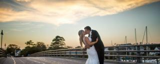 Bride and groom kissing on bridge at sunset at Roanoke Island Festival Park