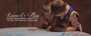 Learn and play in the Adventure Museum graphic featuring two boys looking at a map in the museum at Roanoke Island Festival Park