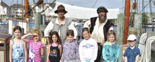 Overnight girl scout group posing with historic interpreters on the Elizabeth II ship at Roanoke Island Festival Park.