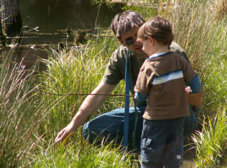 Picture of man and little boy in tall grass by water.