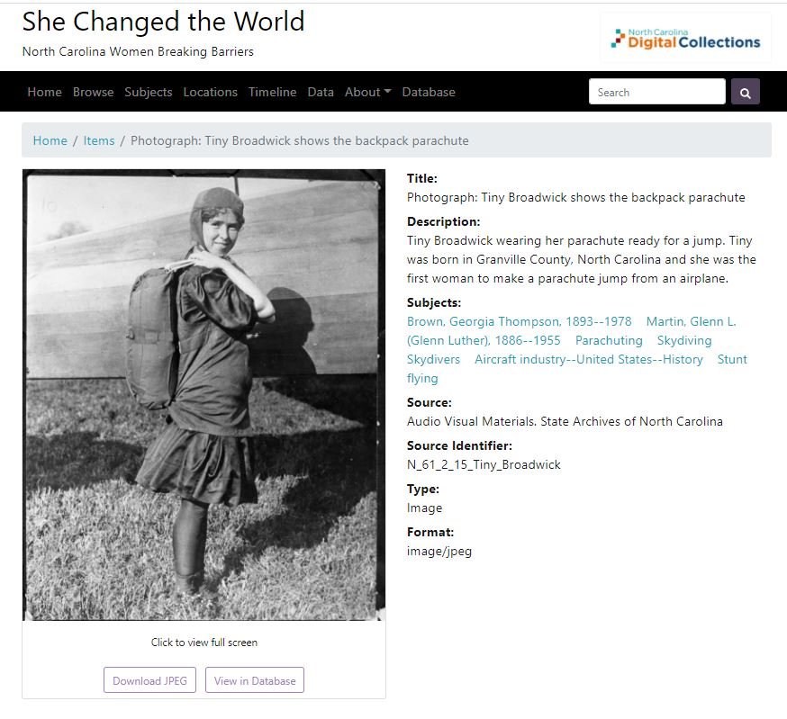 screen shot of She Changed the World - showing image of Tiny Broadwick standing, wearing backpack parachute