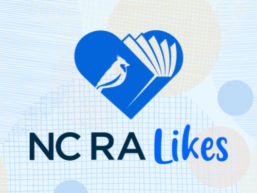 An image of a blue book shaped like a heart with a cardinal on the front cover and the words NC RA Likes underneath