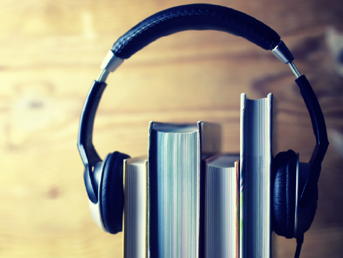 Photo of books stacked upright with a headset over them