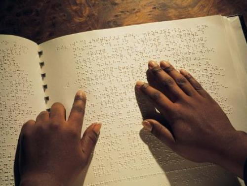Photo of hands moving across a braille book