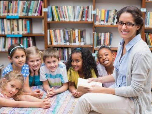 Photo of Librarian reading to children in Library