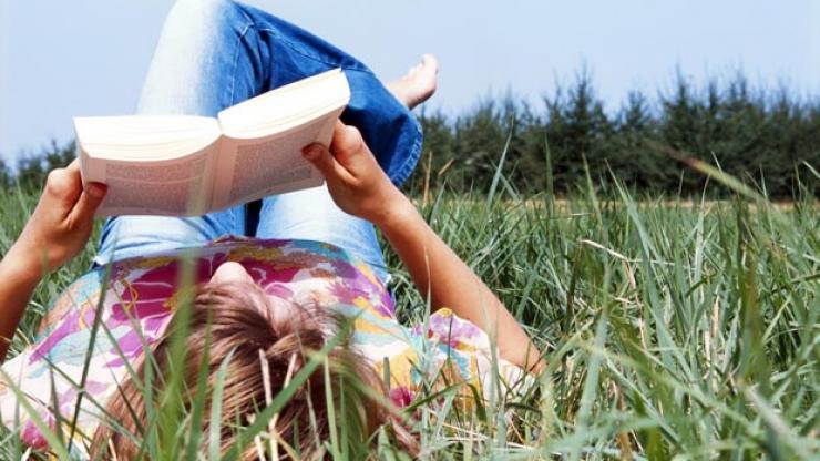 A reader lays down in the grass on sunny day with a book held above their head