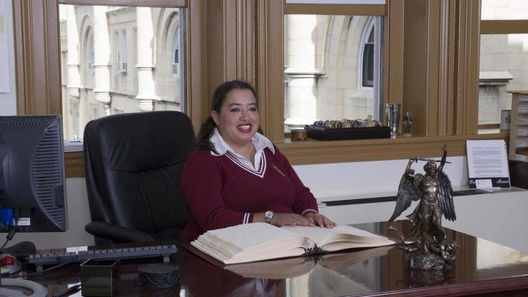 A woman in a red sweater and collared shirt sits at a desk reading a braille copy of a book