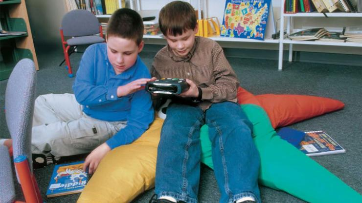 Two boys sit side by side on a floor in a library reading area listening to a talking book on a digital talking book player