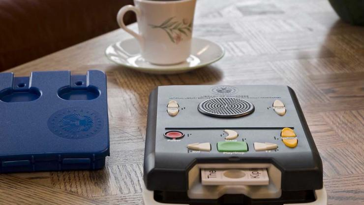 An NLS Digital Talking Book player sits on a table. To its right is Digital Talking Book Cartridge. Behind it is a cup of coffee