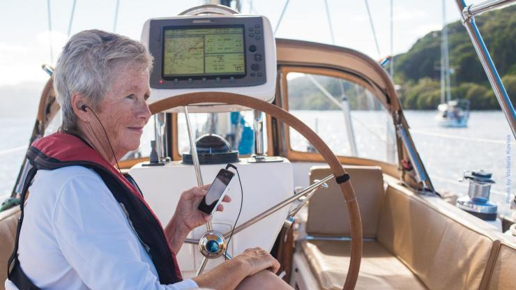 A woman sits on a sailboat listening to a BARD Mobile book on her smartphone