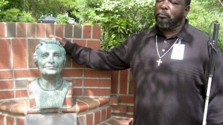 A man stands by a brick wall with a fountain statue of Helen Keller