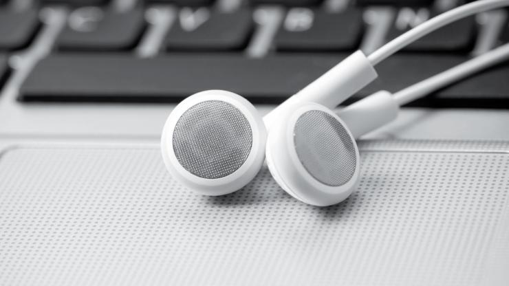 a pair of earbuds sit on a laptop's track pad