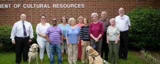 A library's Friends Group Board stand in front of the library building