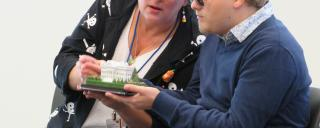 Attendees hold a scale model of the White House