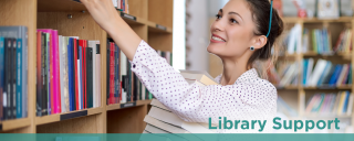 Female librarian shelving books in library below text library support