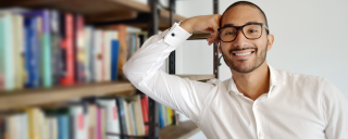 Smiling male librarian leaning against a stack of book in library