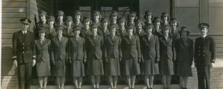 Three rows of women in World War II uniforms standing on steps with one man in uniform on either side