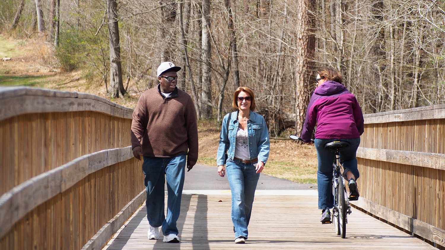 A biker and two hikers enjoy the Mountains-to-Sea State Trail section in Clayton.