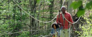 A family crosses the suspension bridge at Eno River State Park.