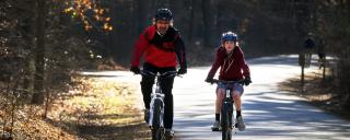 A father and a son ride their bikes on the multi-use trail at William B. Umstead State Park.
