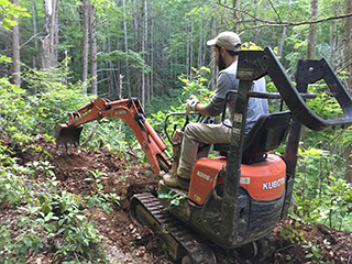 Trails Specialist Matt Lawson uses a mini-excavator to clear trees for a trail.