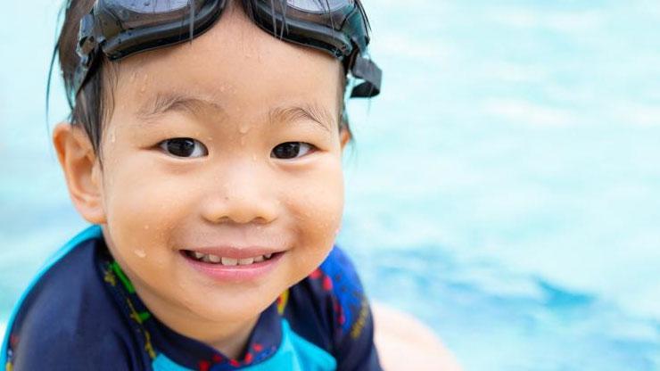 Child sitting next to pool