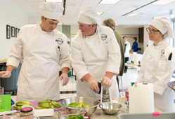 Photo of Caliente Cowboys and Cowgirl chefs preparing a dish.