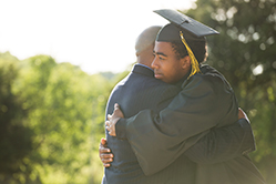 Father hugging son with his graduation cap and gown