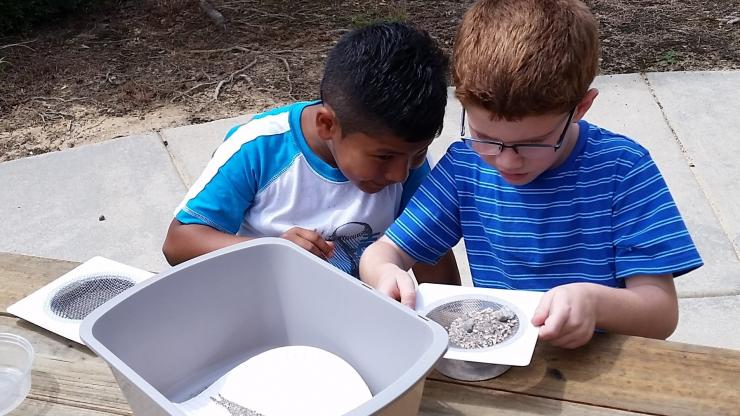 Preschoolers sifting rocks