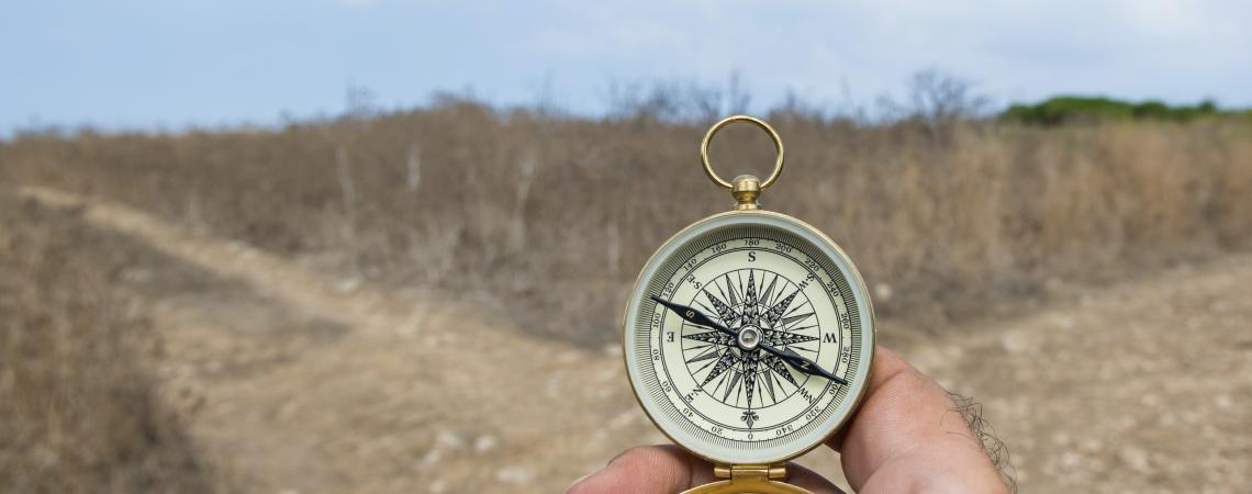 Hand holding compass at cross roads
