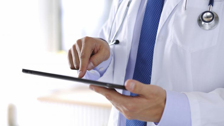 Doctor looking at medical data on a tablet