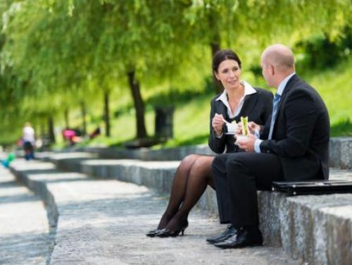 two people eating lunch together sitting on a concrete wall outside