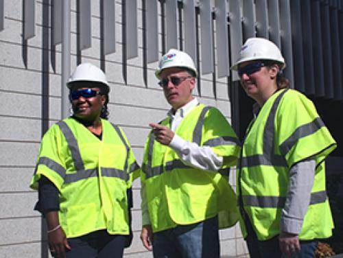 Three people in construction vests and hard hats looking in the same direction