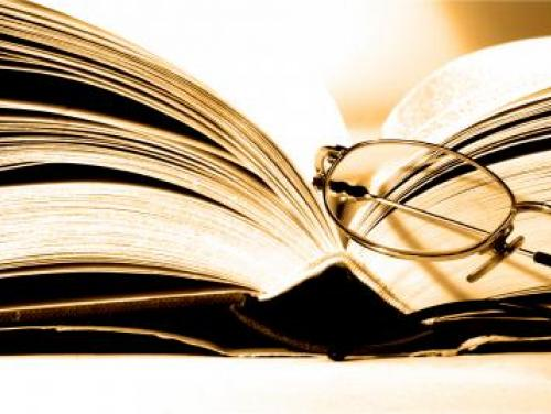An open book with glasses leaning on it