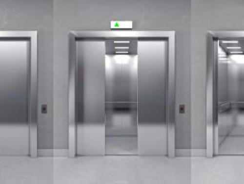 Three elevators side by side with the middle elevator doors slightly open and the right elevator doors completely open