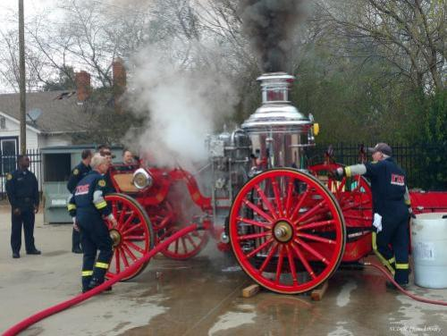 people gather around a historical fire department boiler