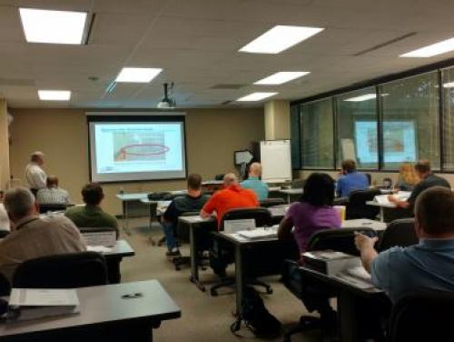A classroom full of people watching a presentation for OSH training