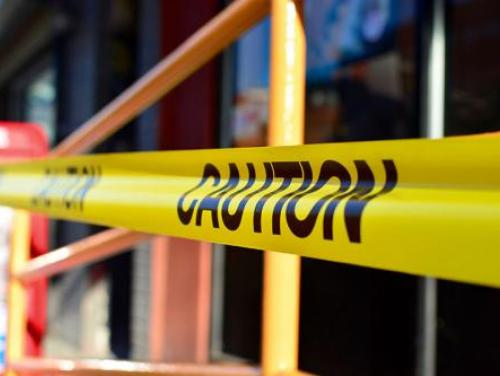 Caution tape close-up across a railing outside a building