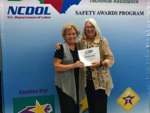 Commissioner Berry poses with a person at a Safety Awards Banquet in front of a blue backdrop