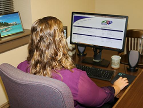 A youth employee sits at their computer and fills out a Youth Emloyment Certificate