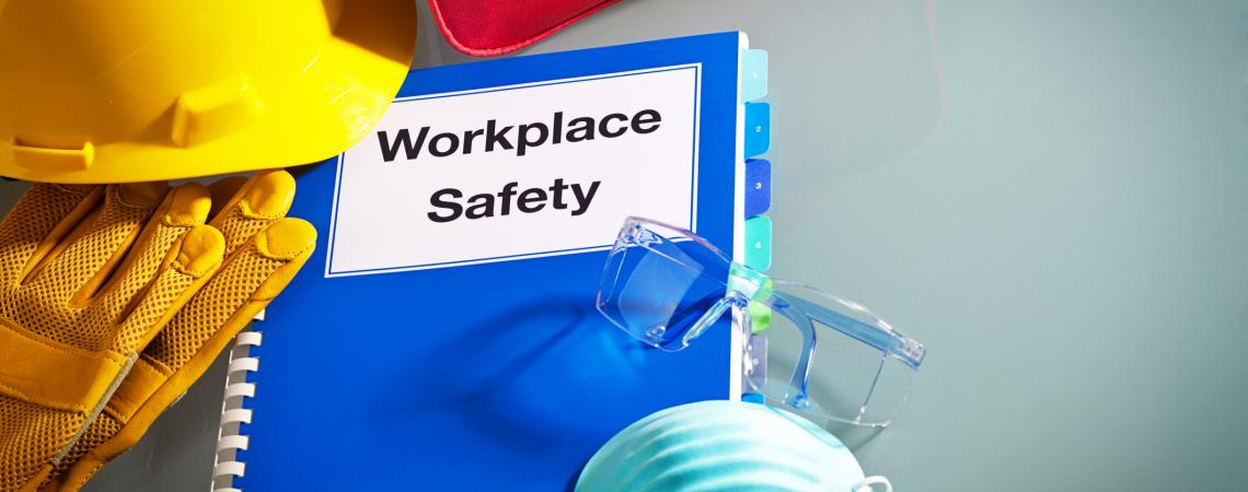 """A blue notebook says """"workplace safety"""" surrounded by a first aid kid, a respiratory mask and a hard hat."""