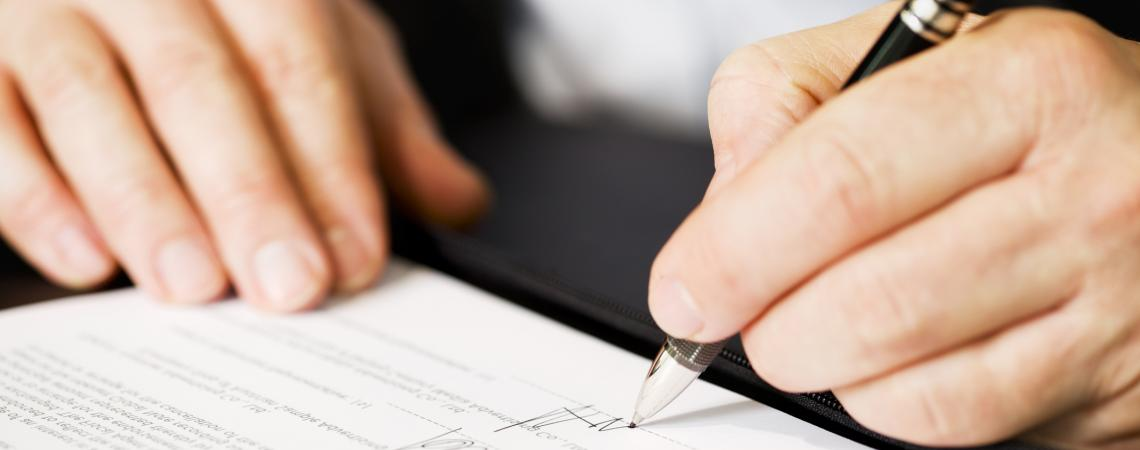 person signing a form, close-up on hands