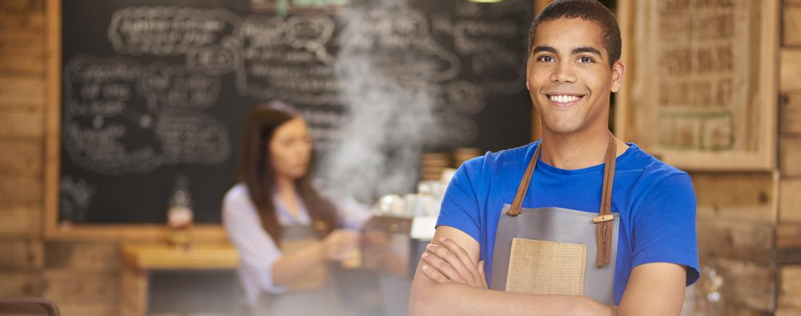 a youth employee wearing an apron with arms crossed and smiling