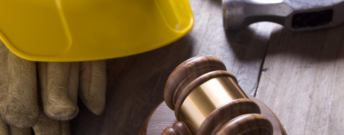 a gavel sits next to a hard hat, gloves and a hammer