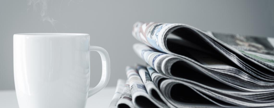 stack of newspapers next to a hot cup of coffee