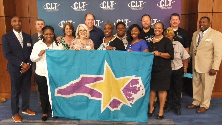 A group of people pose with Commissioner Berry while holding the Carolina Star flag