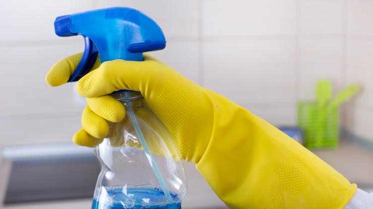 A hand in a yellow glove holding a spray bottle