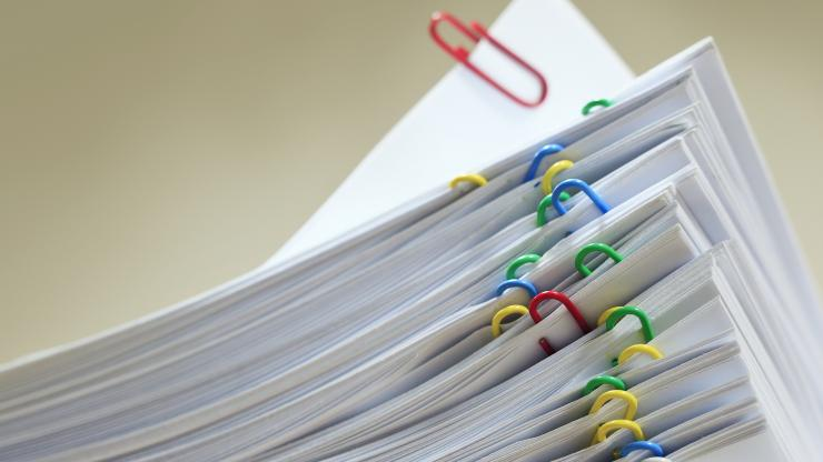 A stack of paper with multi-colored paperclips