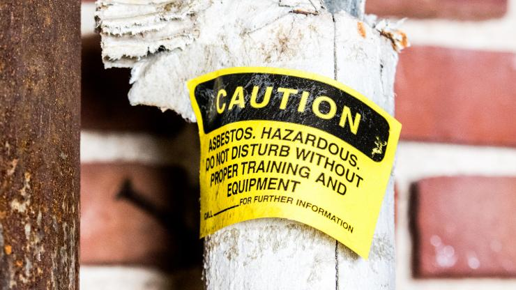 A caution sticker warning about asbestos over a brick and wood wall