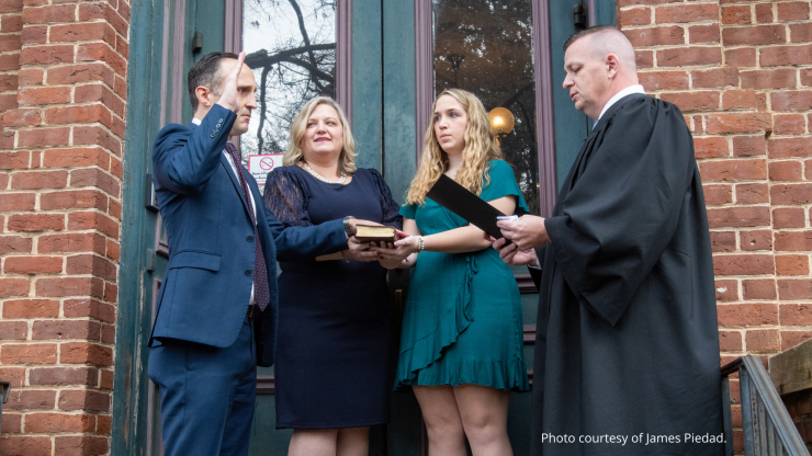 Labor Commissioner Josh Dobson stands on the front steps of the red brick Labor Building with his wife, daughter, and an N.C. Supreme Court Justice.